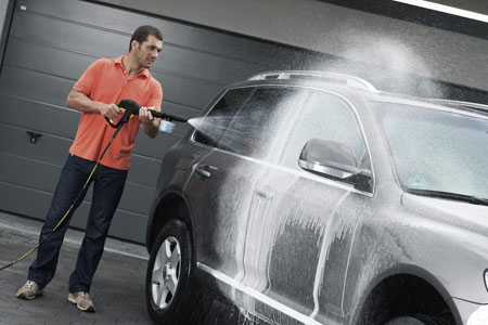 на фото человек моет машину автомойкой высокого давления